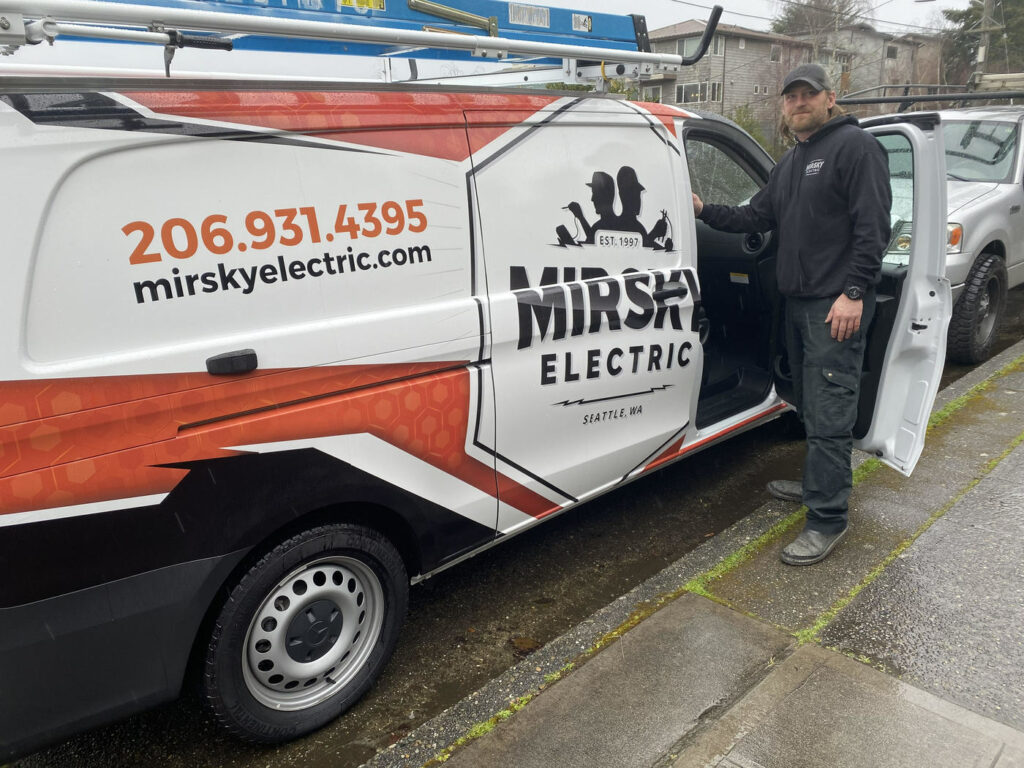 Photo of an Mirsky Electric employee standing next to his work van